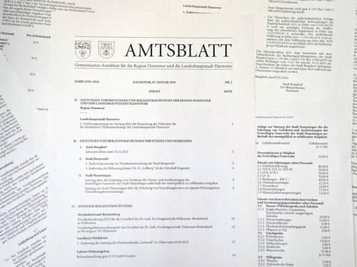 """Amtsblatt: Bedruckte Papierbögen liegen neben- und aufeinander, auf dem obersten steht in der Kopfzeile """"AMTSBLATT"""""""
